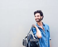 Smiling man holding travel bag and looking over shoulder Stock Photos