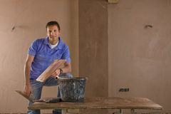 Smiling man holding trowel next to bucket of plaster Stock Images