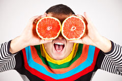 Smiling man holding two grapefruits in hands. Young man holding slices of grapefruits to his eyes on white background Royalty Free Stock Photos