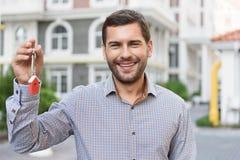 Smiling man holding up keys Stock Image