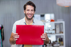 Smiling man holding up red blank sign Royalty Free Stock Photo