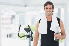 Smiling man holding water bottle at spinning class in bright gym Stock Photos