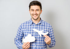 Smiling man holding white paper model of plane and cloud Stock Image