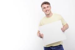Smiling man holding white sheet of paper Stock Photos