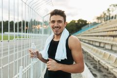 Smiling man holding white towel and bottle of water. Close-up portrait of a handsome sports man looking at camera. Young handsome well formed sporty man Royalty Free Stock Photo