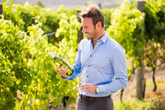 Smiling man holding wine bottle and glass Royalty Free Stock Images