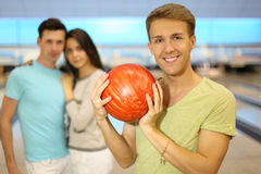 Smiling man holds ball; pair stands behind him Royalty Free Stock Photos