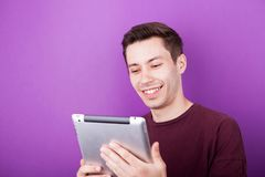 Smiling man holds a digital tablet PC in his hands. On purple background in studio photo Stock Photos