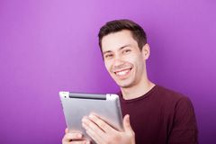 Smiling man holds a digital tablet PC in his hands. On purple background in studio photo Royalty Free Stock Image