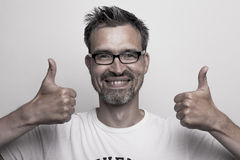 Smiling man holds his thumbs up. Smart man holds up his thumbs while smiling into the camera royalty free stock image