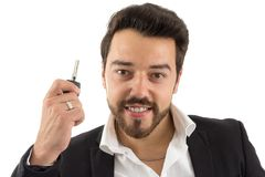 Smiling man holds up the car key. bearded person wears black jac. Happy man presents the new car key. Concept of leasing, rental of vehicle, new car. Beautiful Stock Images