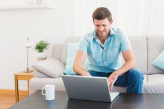 Smiling man at home on a laptop Stock Image