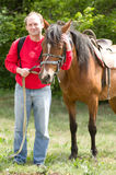 Smiling man with horse in the forest. Handsome smiling man with horse in the forest Royalty Free Stock Photography