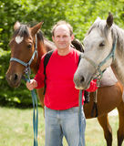 Smiling man with horse in the forest Royalty Free Stock Images