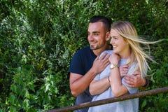Smiling man hugging blonde girlfriend behind gate Royalty Free Stock Photography