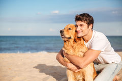 Smiling man hugging his dog on the beach in summer Royalty Free Stock Photo