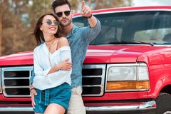 Smiling man hugging his girlfriend and pointing somewhere while standing. Near red jeep stock image