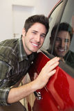 Smiling man hugging a red car Royalty Free Stock Photo