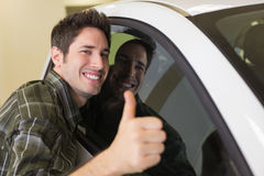 Smiling man hugging a white car while giving thumbs up Stock Photo