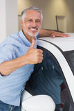 Smiling man hugging a white car while giving thumbs up Royalty Free Stock Photo