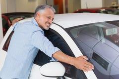 Smiling man hugging a white car Stock Photo