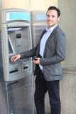 Smiling man introducing PIN at ATM Royalty Free Stock Photography