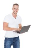 Smiling man in jeans using a laptop computer Stock Photos