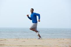 Smiling man jogging at the beach Royalty Free Stock Photos