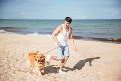 Smiling man jogging with his dog on the beach Royalty Free Stock Photography