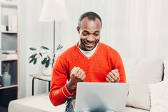 Smiling man jubilating in front of laptop. Portrait of content african guy rejoicing while sitting with gadget in comfortable living room Royalty Free Stock Photo