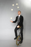 Smiling man juggles balls. Sitting on a unicycle Royalty Free Stock Photo