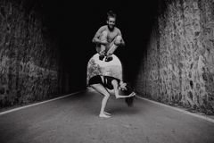 Smiling man jumping over his girlfriend while playing on a road. Black and white. Couple playing jumps black and white portrait Royalty Free Stock Images