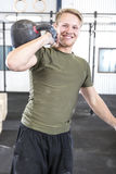 Smiling man with kettlebell at fitness gym Stock Images