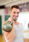 Smiling man with kettlebell in gym Royalty Free Stock Images