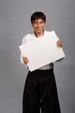 Smiling man in kimono with card. Smiling man in kimono on grey background with business card Stock Image