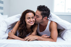 Smiling man kissing woman while lying under blanket Royalty Free Stock Photo