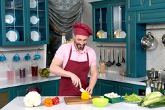 Smiling man at kitchen cutting yellow paprika in apron and hat. Smiling Chef in red apron and cap at kitchen cutting yellow paprika for salad on cutting board Royalty Free Stock Photos