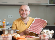 Smiling man in  kitchen preparing meat Royalty Free Stock Image