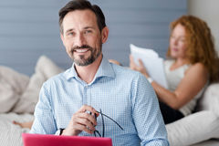 Smiling man with laptop on background of woman Stock Photography