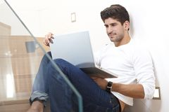 Smiling man with laptop computer at home Royalty Free Stock Images