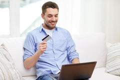 Smiling man with laptop and credit card at home Royalty Free Stock Photo
