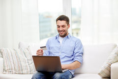 Smiling man with laptop and credit card at home Stock Photo