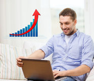 Smiling man with laptop and growth chart at home Royalty Free Stock Image