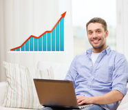 Smiling man with laptop and growth chart at home Royalty Free Stock Photos
