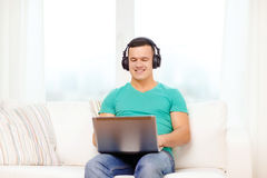 Smiling man with laptop and headphones at home. Technology, home, music and lifestyle concept - smiling man with laptop and headphones at home royalty free stock image