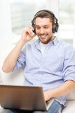 Smiling man with laptop and headphones at home Stock Photography