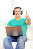 Smiling man with laptop and headphones at home Royalty Free Stock Photos