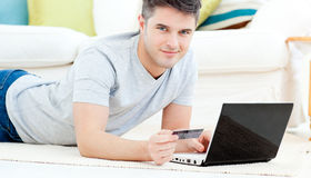 Smiling man with laptop holding a card Royalty Free Stock Photos