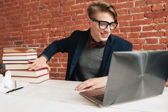 Smiling man with laptop move away pile of books Royalty Free Stock Images