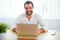Smiling man with laptop in office Royalty Free Stock Images